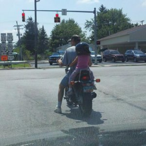 4-year old biker babe riding with [presumed] her daddy